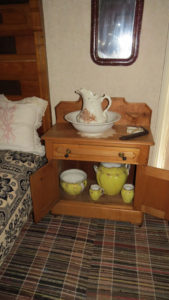 Commode with pitcher and bowl and chamber pot among items in cupboard