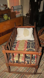 Baby's cradle with pillow and antique jacquard quilt